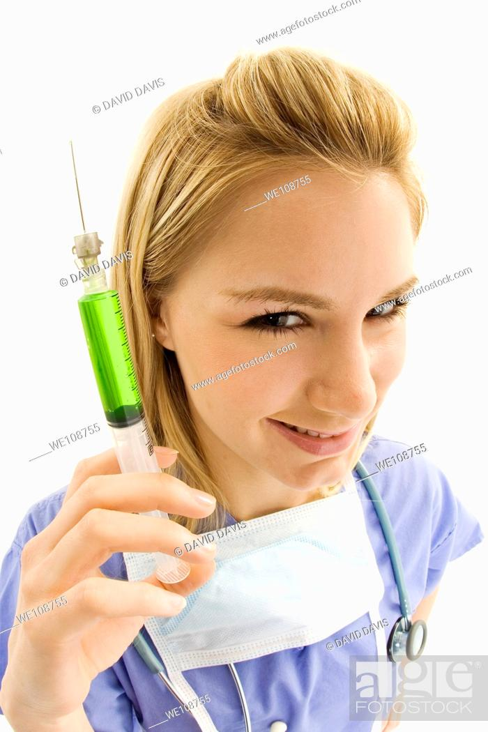 Stock Photo: Young caucasian female nurse wearing scrubs outfit and holding a syringe.