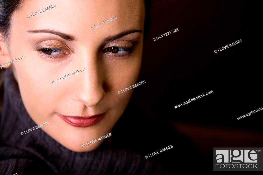 Stock Photo: A mid adult woman looking away, close-up.