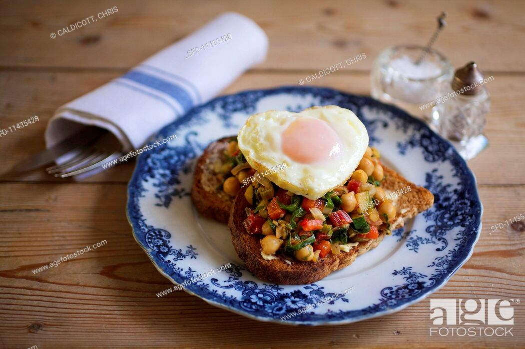 Stock Photo: A slice of toast topped with tomatoes, chard, chickpeas and a heart-shaped fried egg.