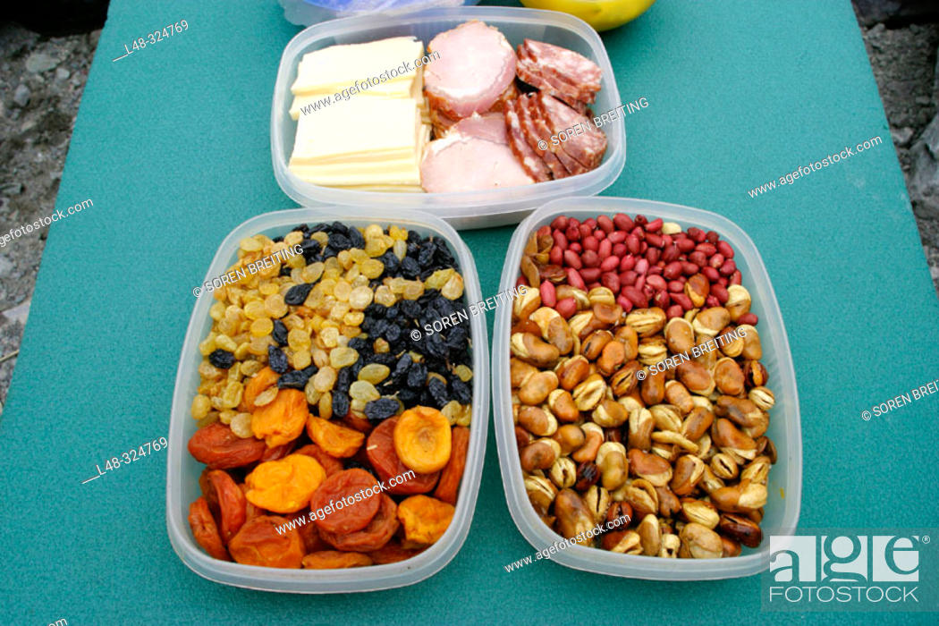 Stock Photo: Plastic containers with snacks of dried raisins, apricots, different nuts, ham, sausage and cheese ready for the hungry hiker during a hike in the mountain.