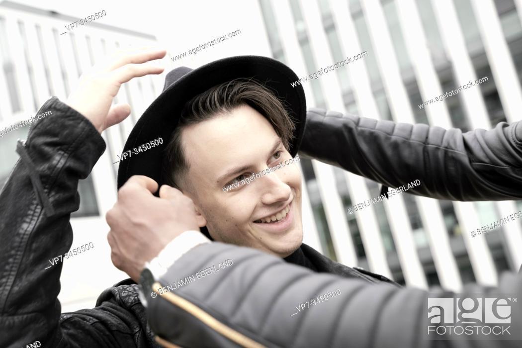 Stock Photo: Man adjusting friend's hat. Munich, Germany.