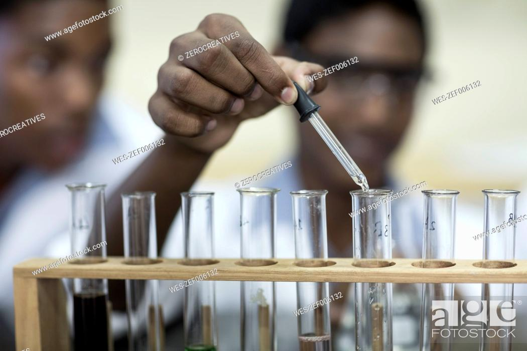 Imagen: Student in chemistry class pipetting liquid into test tube.