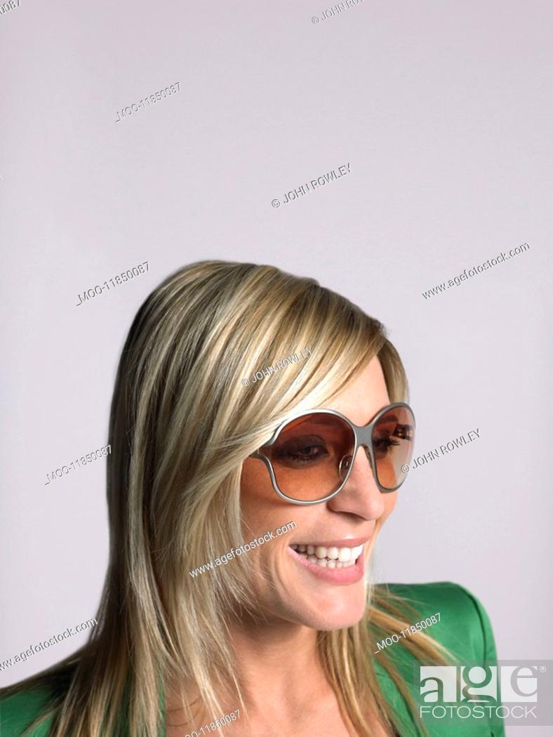 Stock Photo: Woman with blonde hair and sunglasses in studio.