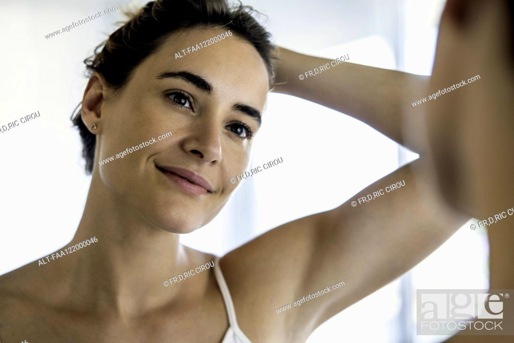 Stock Photo: Young woman looking in mirror.