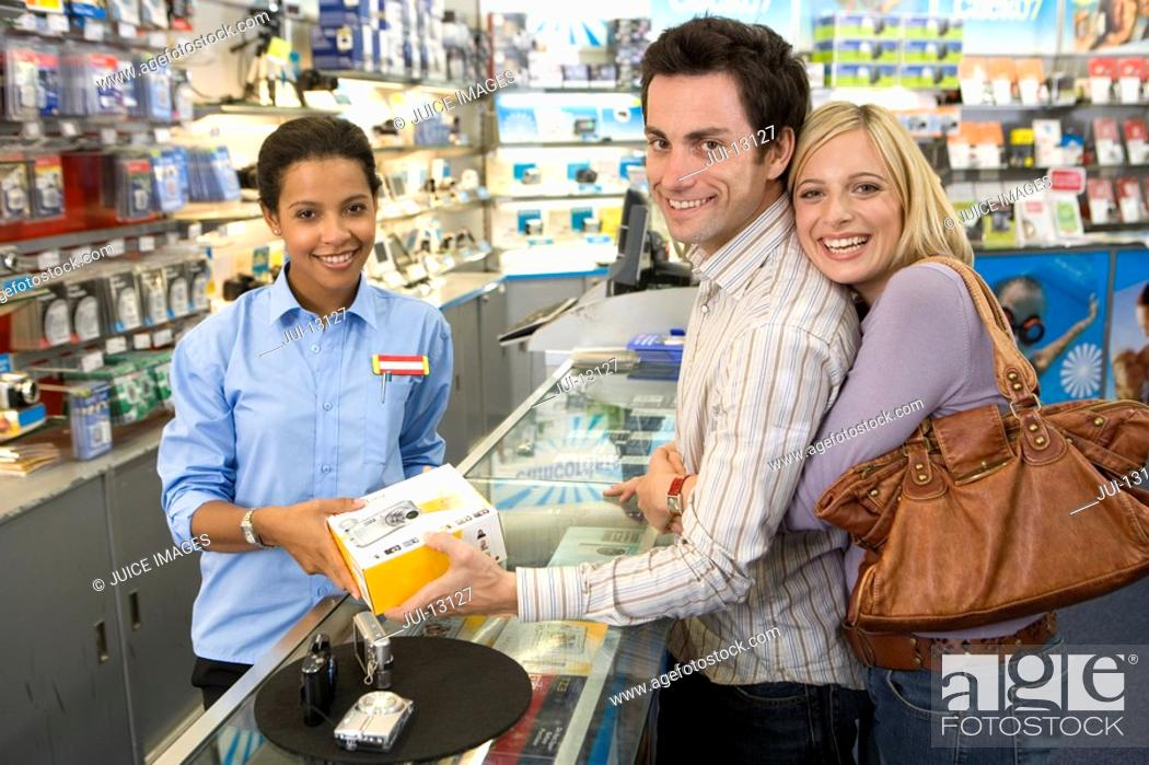 Stock Photo: Young couple with saleswoman buying camera, smiling, portrait, side view.