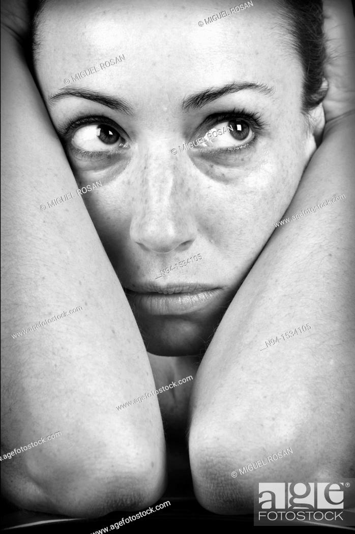 Stock Photo: Closeup of young woman, face resting on her arms and looking sideways.