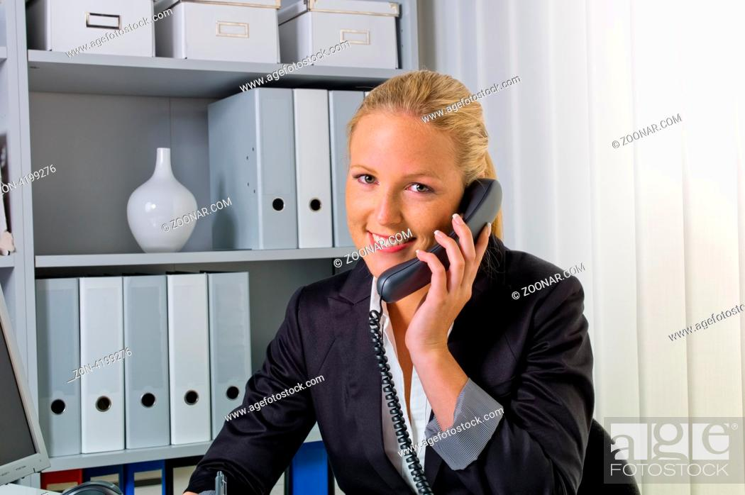 Imagen: Eine freundliche Frau telefoniert an ihrem Schreibtisch im Büro und notiert Termine im Kalender.