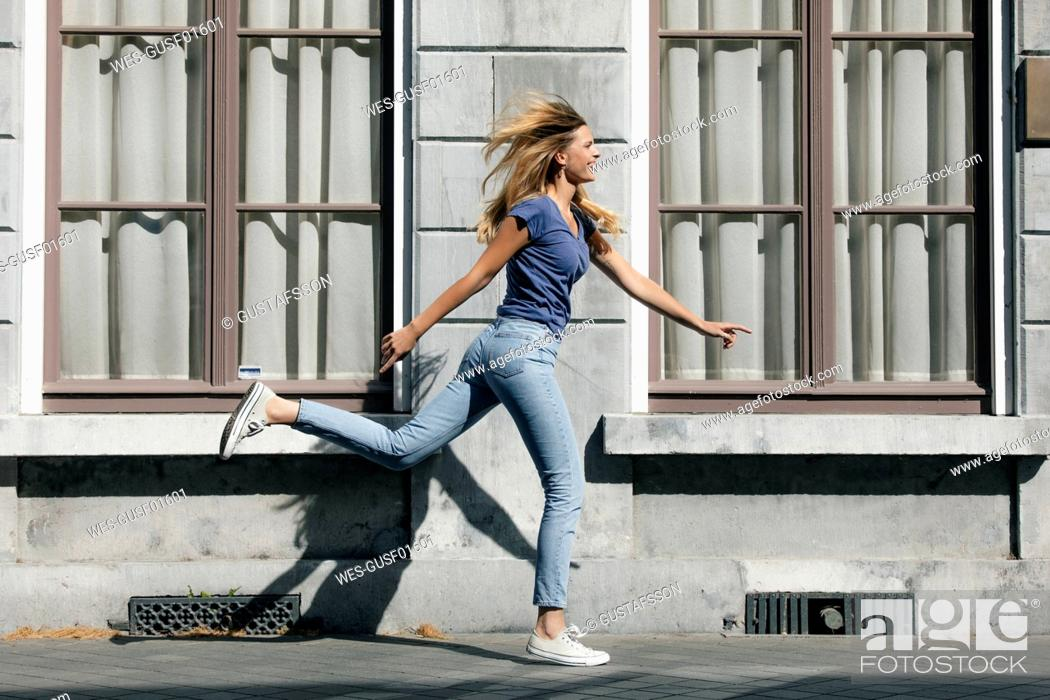 Stock Photo: Netherlands, Maastricht, happy blond young woman running along building in the city.