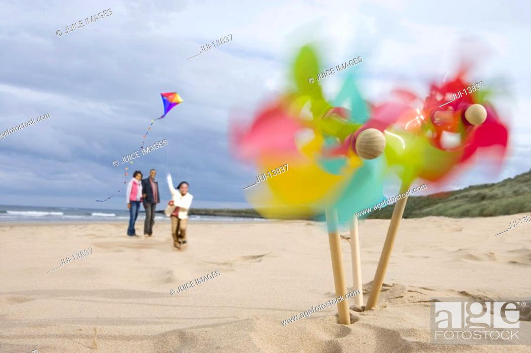Stock Photo: Pinwheels on beach, family with kite in background blurred motion.
