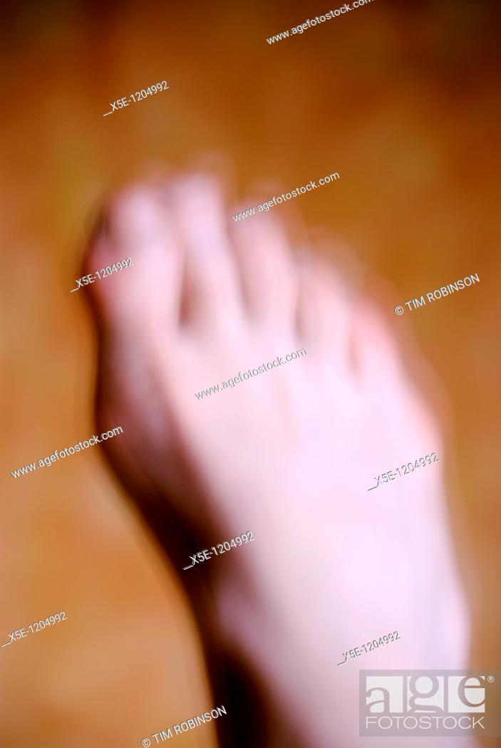 Stock Photo: Bare right foot of adult man, motion blurred.