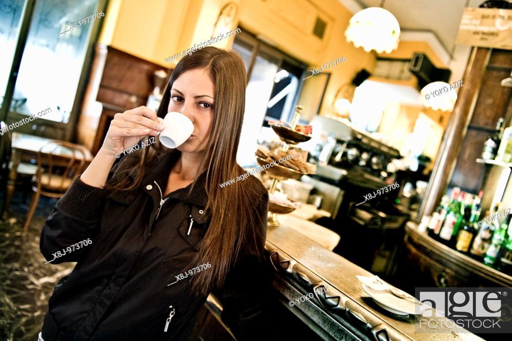 Stock Photo: Young woman at bar, Milan, Italy.