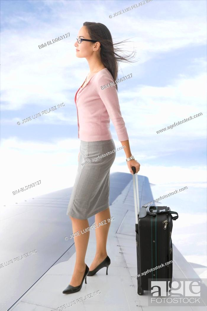 Stock Photo: Mixed race businesswoman standing on airplane wing with suitcase.