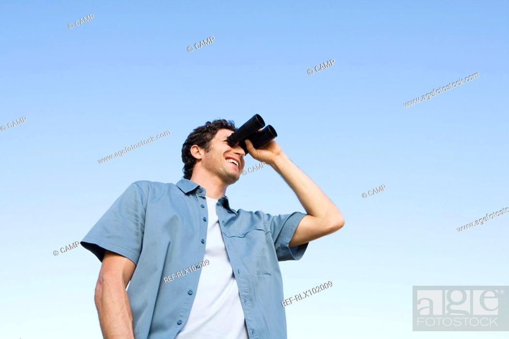 Stock Photo: Man standing outdoors using binoculars.