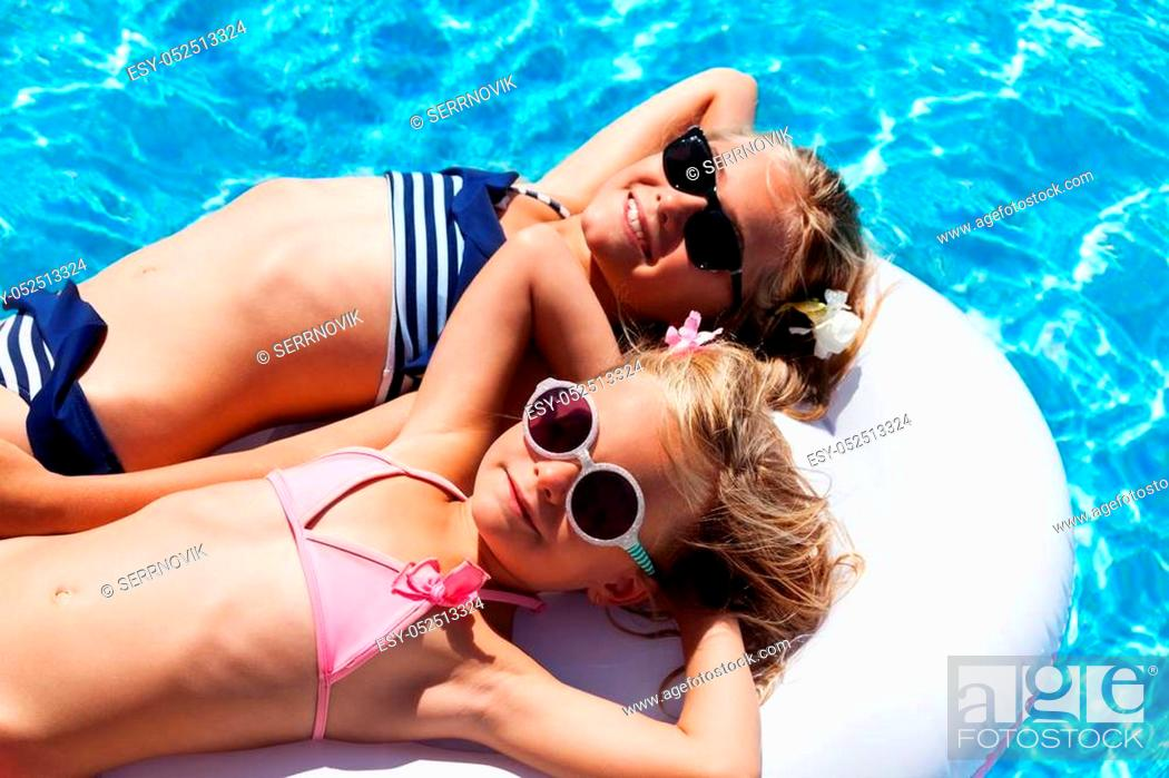 Stock Photo: High-angle shot of two little girls in sunglasses and bikini relaxing on inflatable mattress in swimming pool.