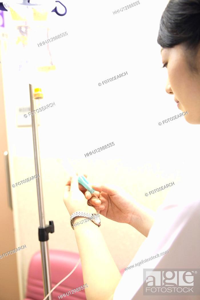 Stock Photo: Nurse preparing for the intravenous feeding.