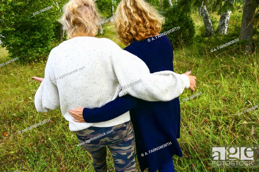 Imagen: Slite, Gotland, Sweden Two women walking arm in arm.