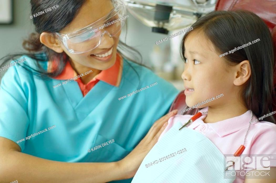 Stock Photo: Indian female dental assistant smiling at young Asian female patient.