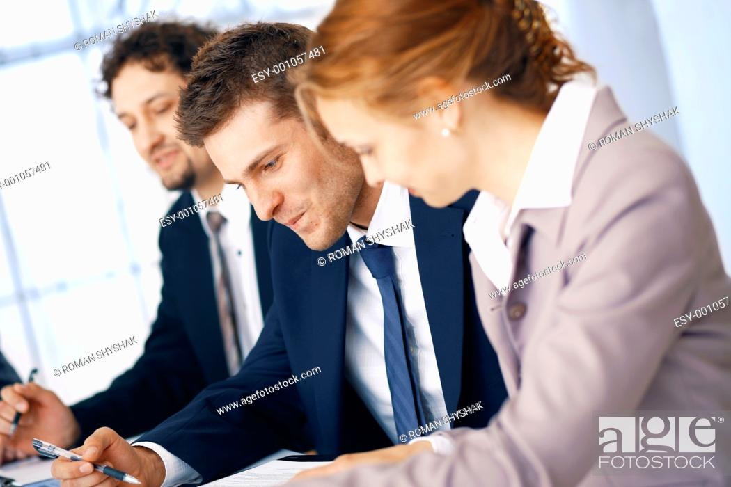 Stock Photo: Group of business people working on some documents at the office.