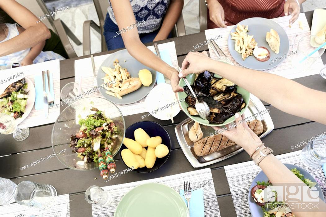 Stock Photo: Family eating together at table outdoors.