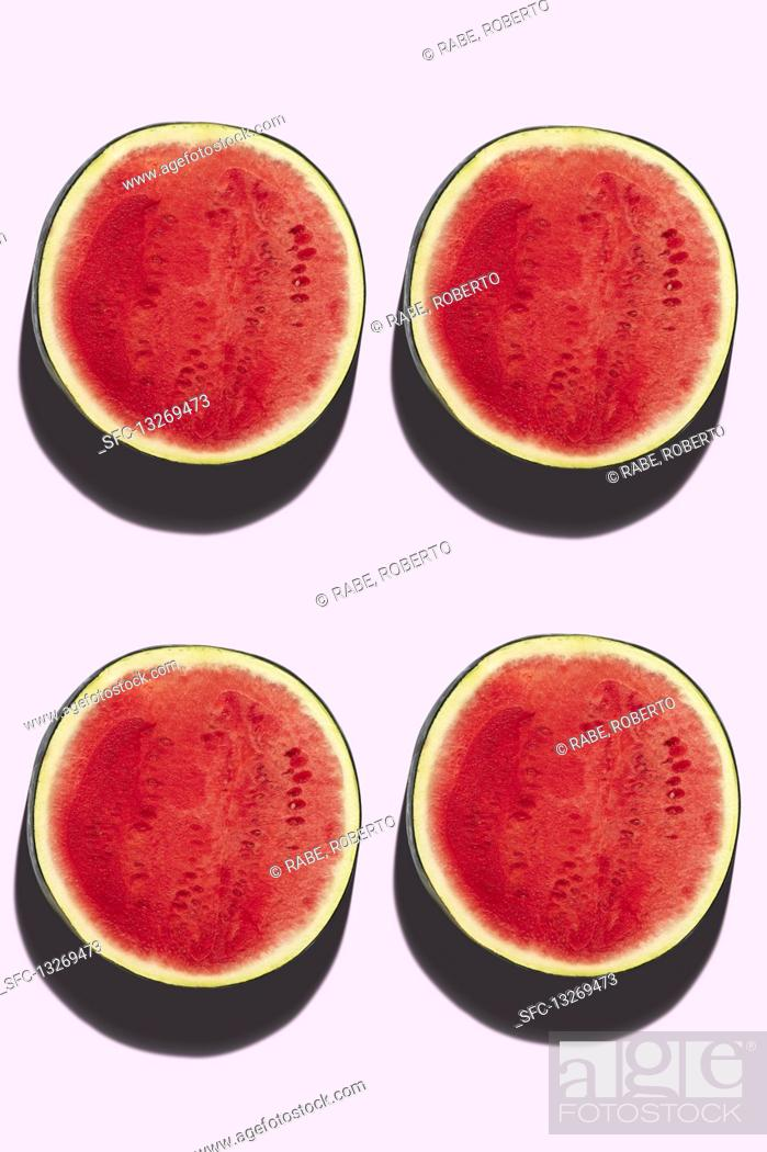 Stock Photo: Four watermelon halves on a pink background.