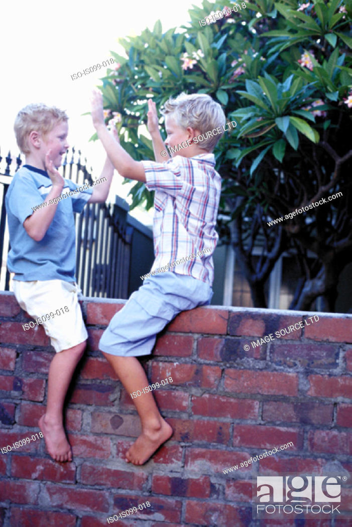 Stock Photo: Boys playing on wall.