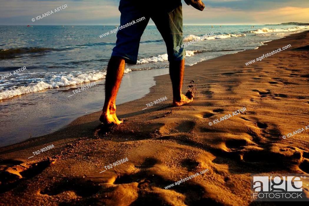 Stock Photo: Young man walking along the beach at sunset.