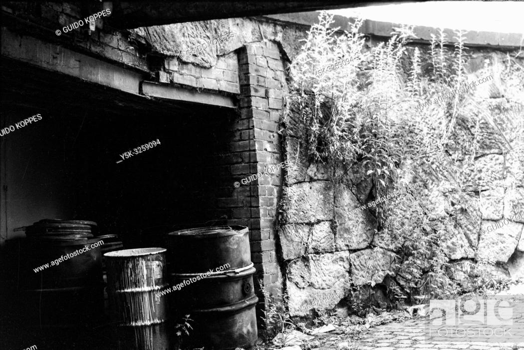 Stock Photo: Chemnitz, former Karl Marx Stadt, East Germany. Old and decomissioned oil drums, stached away in a driveway for collection inside the former DDR town.