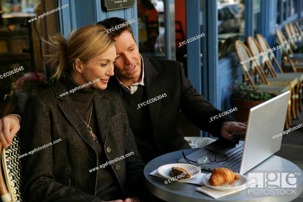Stock Photo: Mature couple outside at a cafe with a laptop.