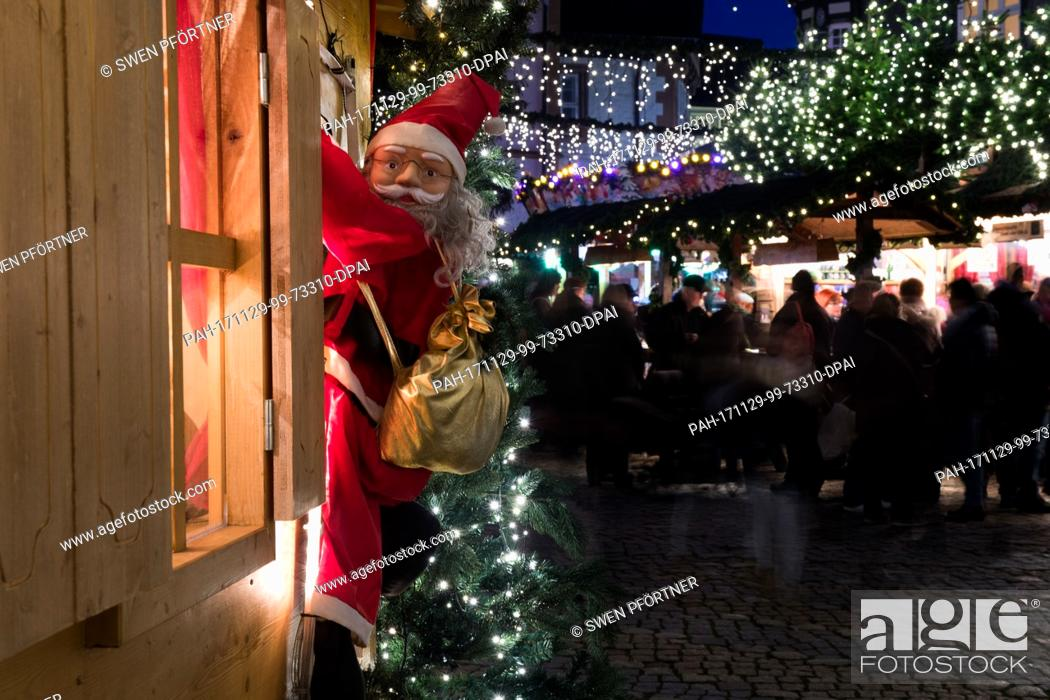 Stock Photo: A Santa Claus figure hangs on the window of a stand at the Christmas market in Goslar, Germany, 29 November 2017. The Christmas market in Goslar is open from 29.