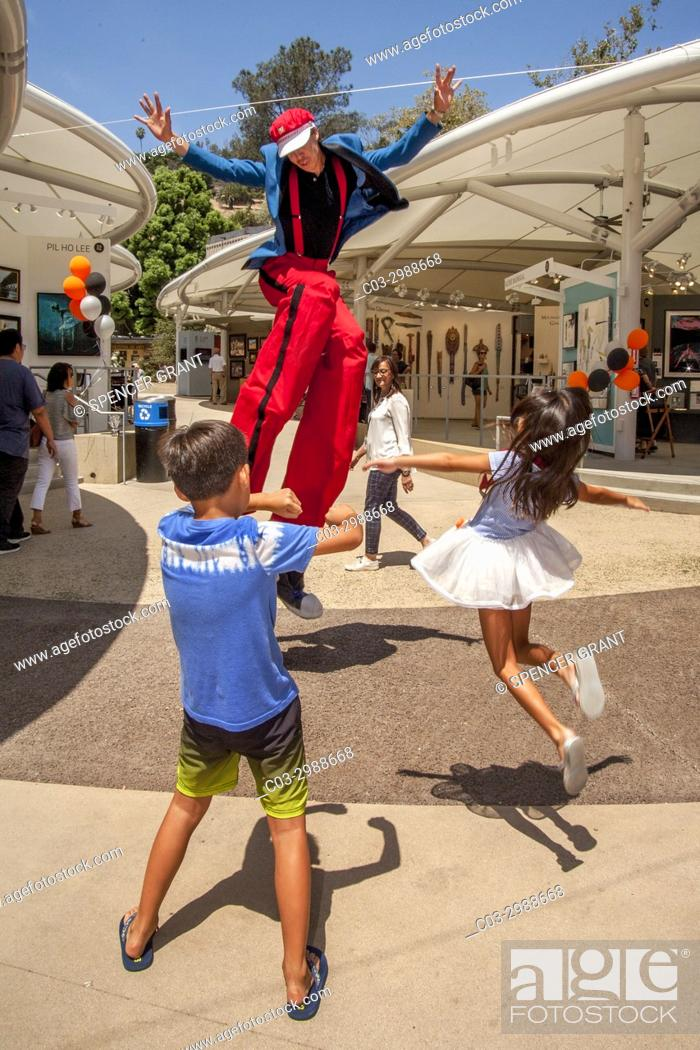 Stock Photo: A costumed stilt walker shares a jump with an exuberant Asian American brother and sister at an art festival in Laguna Beach, CA.