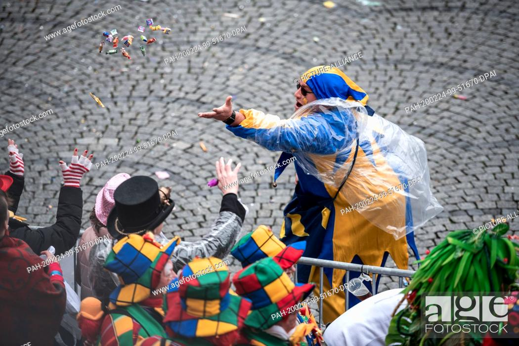 Stock Photo: 24 February 2020, North Rhine-Westphalia, Duesseldorf: A carnivalist throws camels into the audience. With the Rosenmontag parades the Rhenish street carnival.