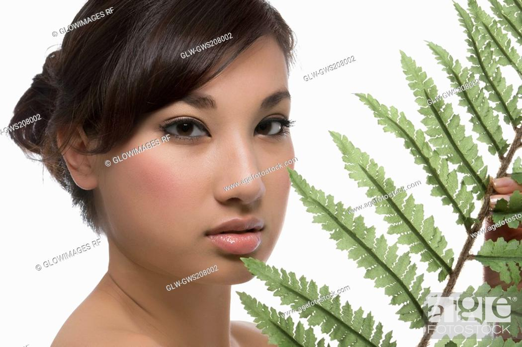 Stock Photo: Portrait of a young woman holding a fern.