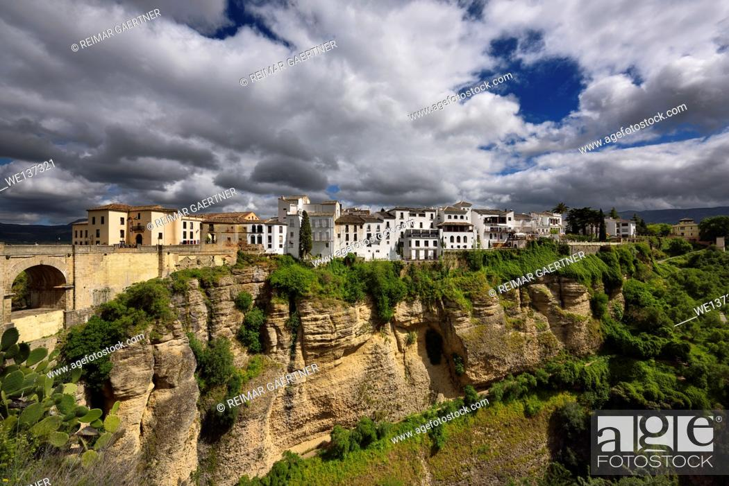 Stock Photo: Sun on white buildings and orange cliffs at El Tajo Gorge Ronda Spain.