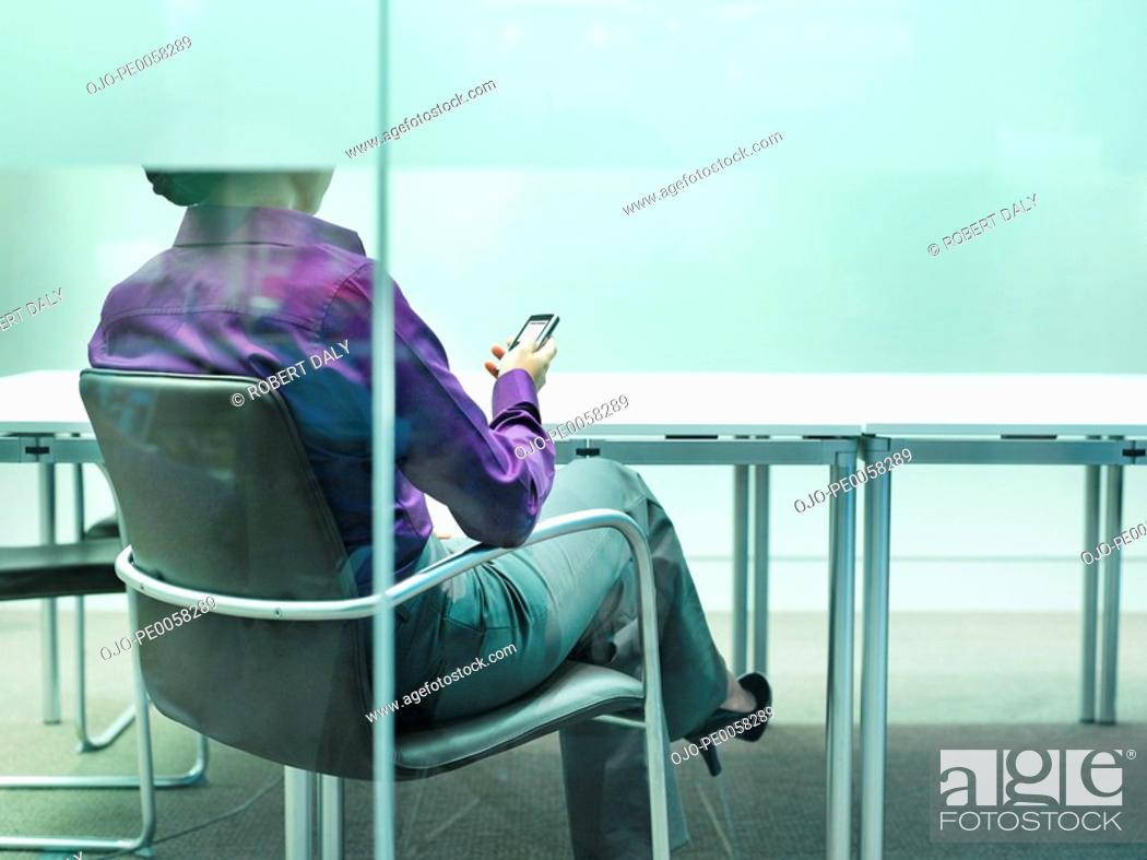 Stock Photo: Businesswoman sitting at desk with mobile phone.