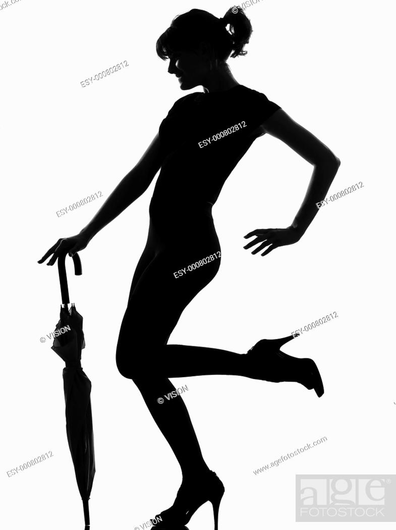 Stock Photo: full length silhouette in shadow of a young woman with closed umbrella in studio on white background isolated.
