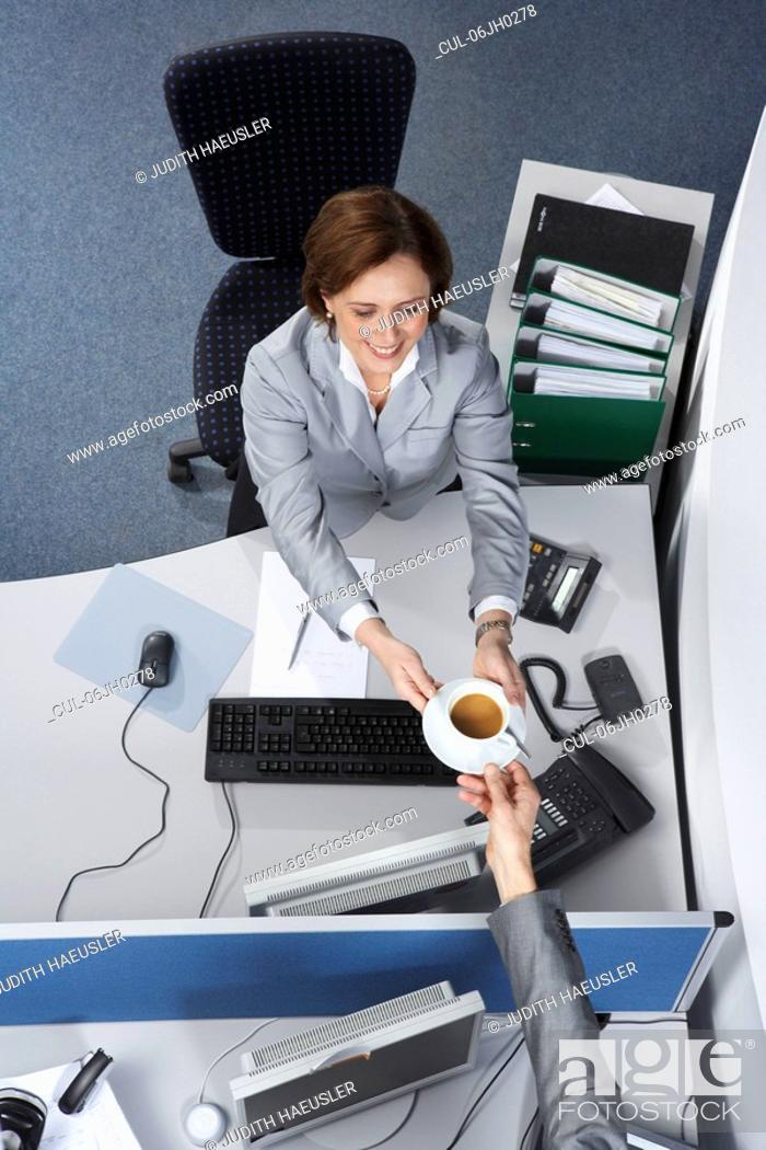 Stock Photo: Businesswoman passing a coffee cup.