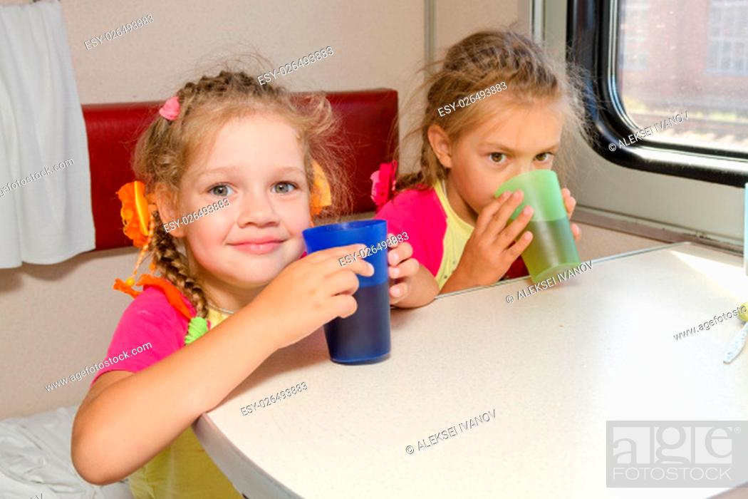 Stock Photo: Two little sisters in a train drinking tea at a table on the lower place in the second-class compartment wagon.