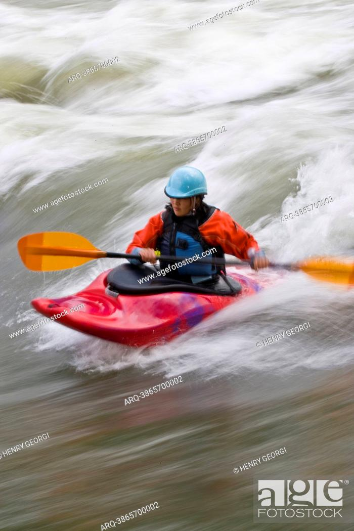 Stock Photo: A young, Asian-looking woman surfing a wave in a whitewater kayak, Elk river, East Kootenies, British Columbia, Canada.