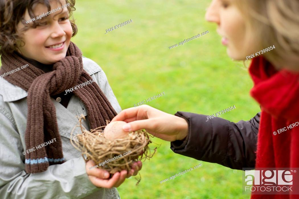 Stock Photo: Boy showing a bird's nest to his mother.