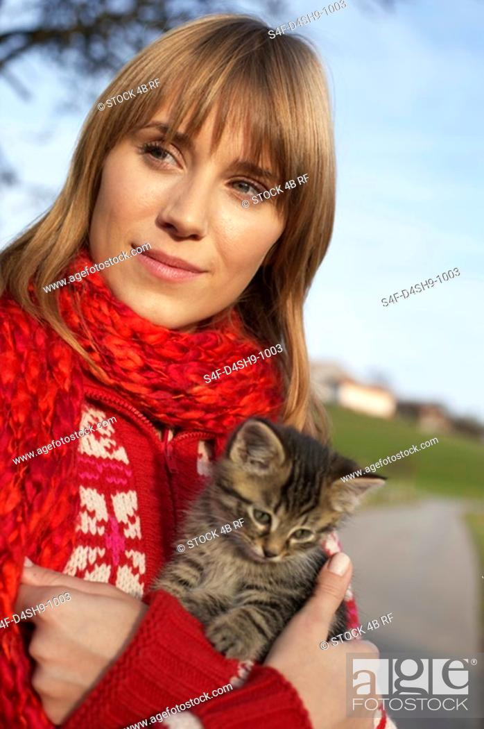 Stock Photo: Young woman with a kitten on her arm, close-up.