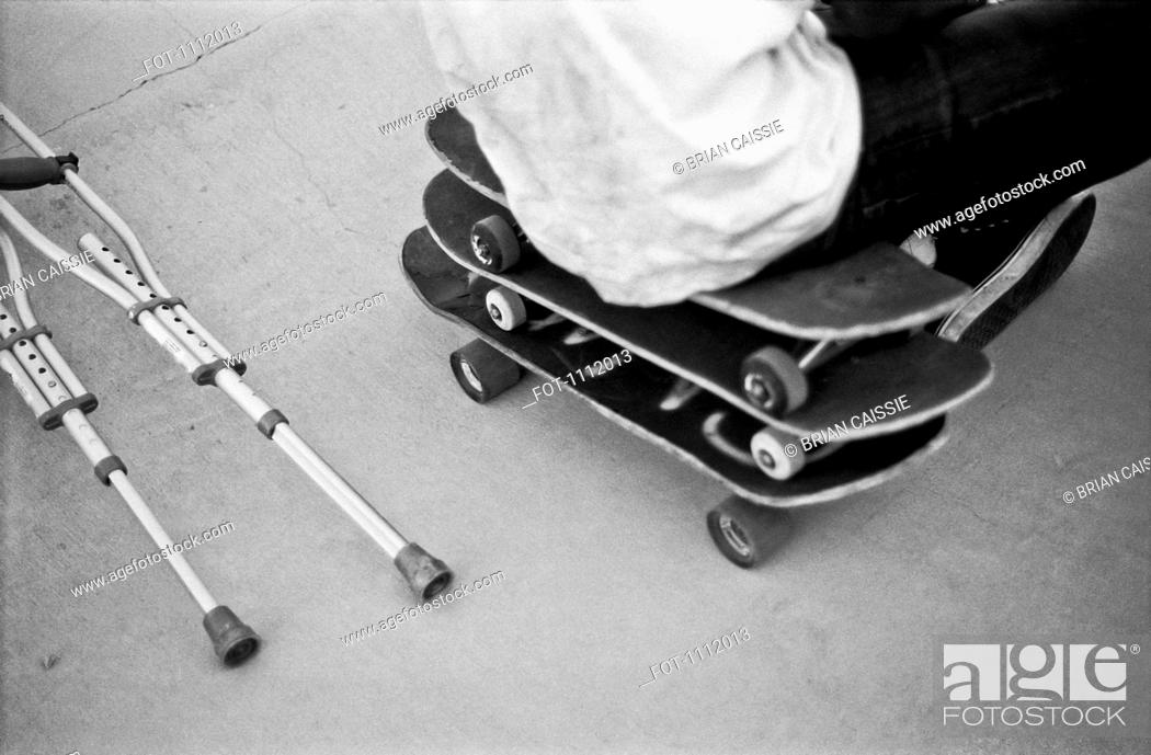 Stock Photo: A man sitting on a stack of skateboards next to crutches.