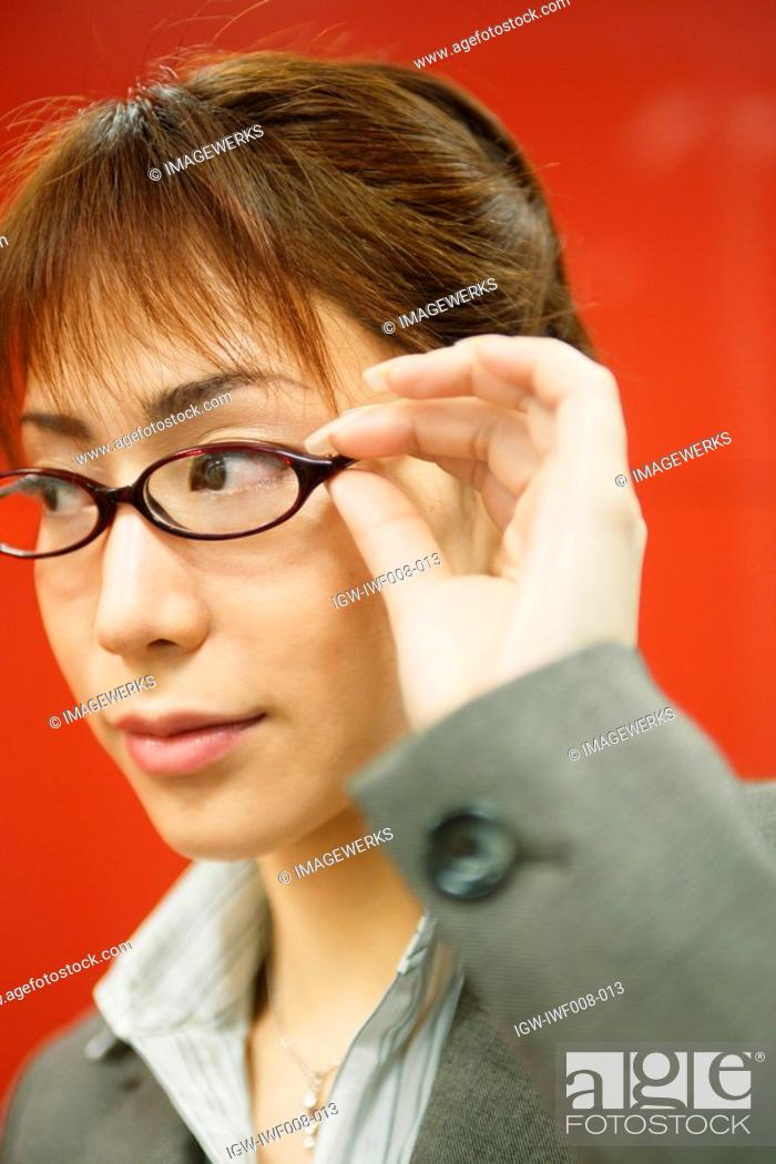 Stock Photo: A businesswoman holding her glasses stares at something.