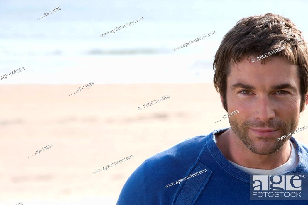 Stock Photo: Man standing on beach, portrait, close-up.