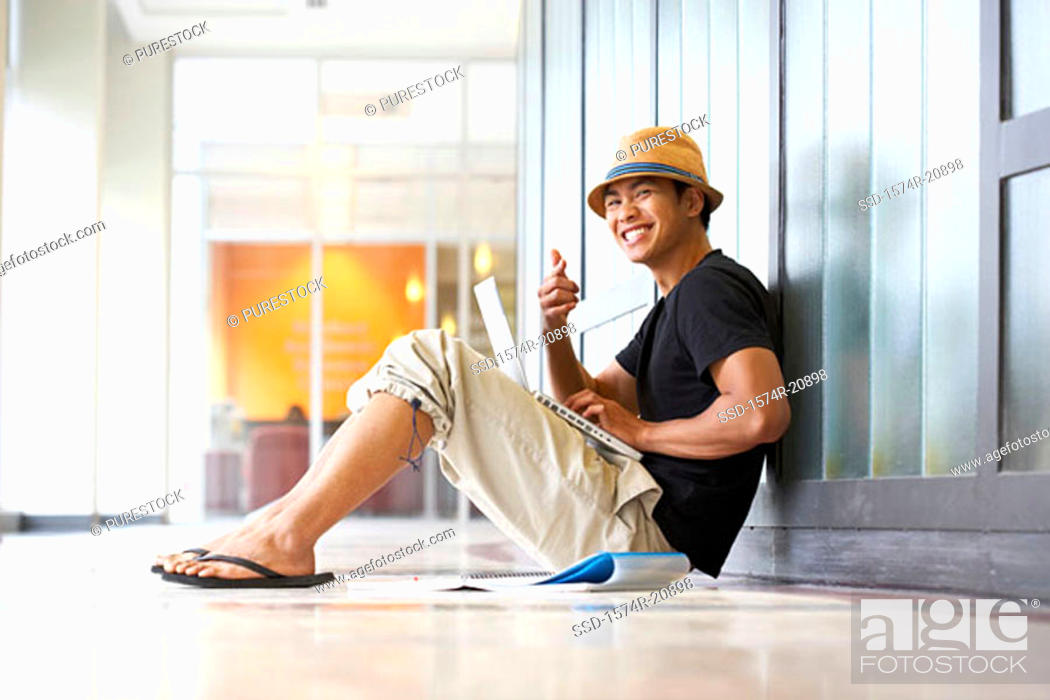 Stock Photo: Portrait of a college student sitting in a corridor with a laptop on his lap.