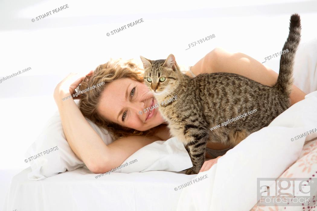 Stock Photo: Attractive young woman in bed with her cat.