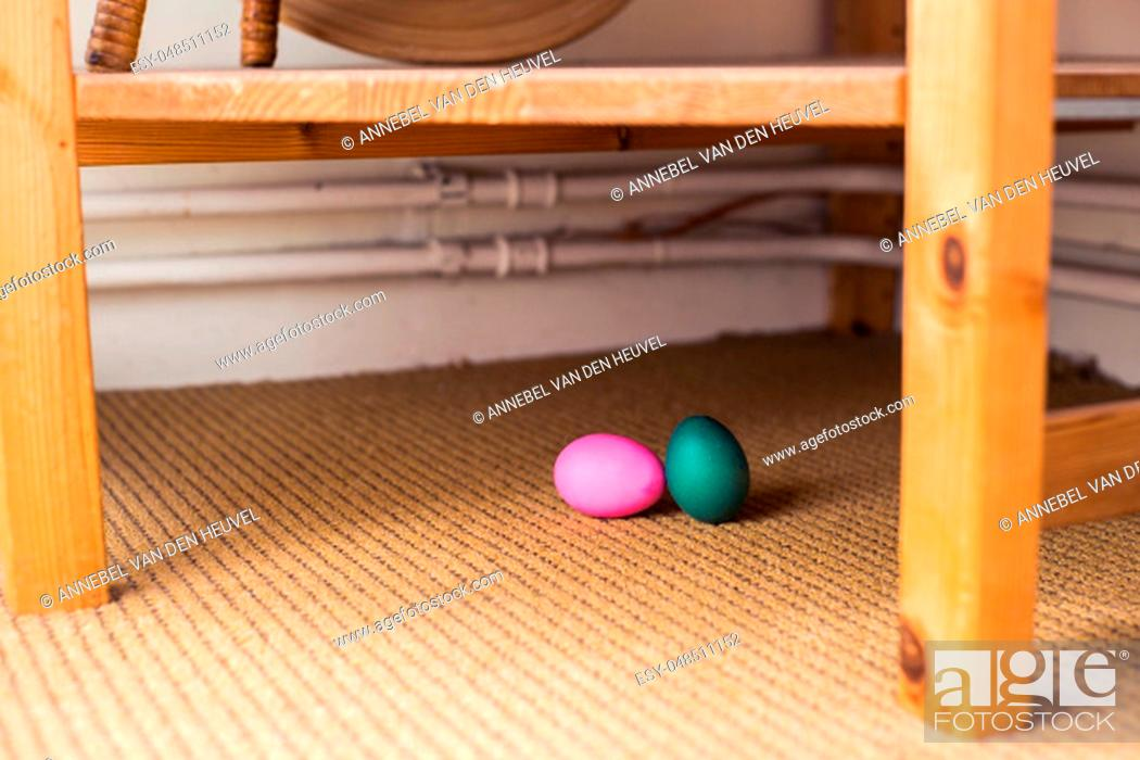 Stock Photo: green and pink dyed Easter egg, hidden for an egg hunt inside a house, april.