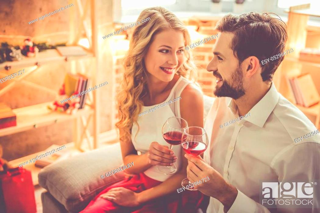 Stock Photo: Beautiful young couple is holding glasses of wine and smiling while celebrating at home.