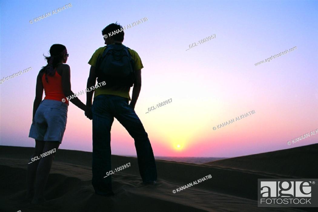 Stock Photo: Western tourist couple watching sunset in the desert, United Arab Emirates.