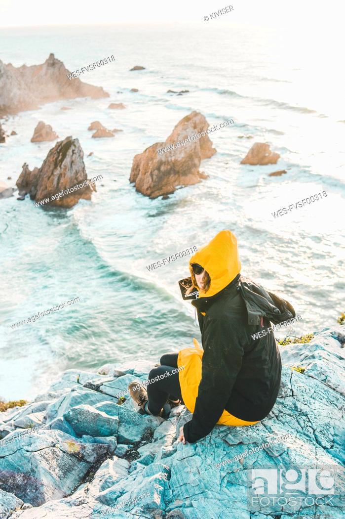 Photo de stock: Young woman in warm clothing sitting on rock at Ursa Beach, Lisboa Region, Portugal.