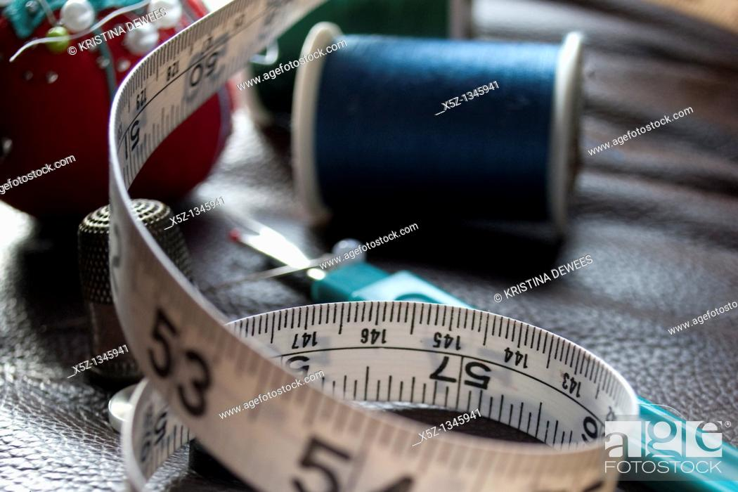 Stock Photo: Some measuring tape and assorted sewing box items.